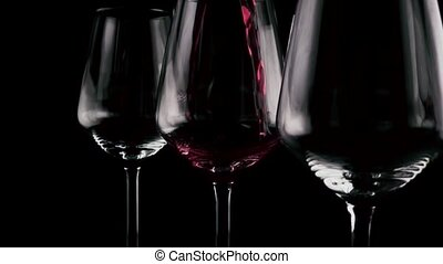 In three glasses wine is poured. Slow motion