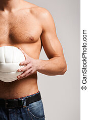 Man holds ball - Photo of shirtless man in jeans holding...