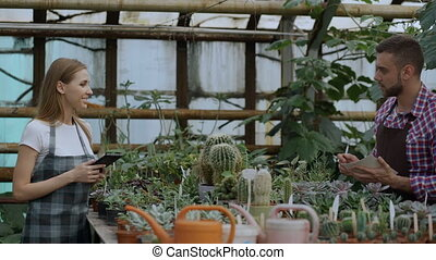 Young couple florists work in garden center. Attractive man...