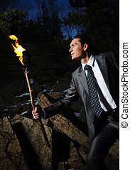 Man with fire - Image of elegant man holding burning stick...