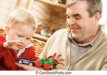 Attention - Portrait of cute kid looking at toy car on his...