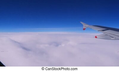 View from a plane window: a plane wing over clouds and blue...