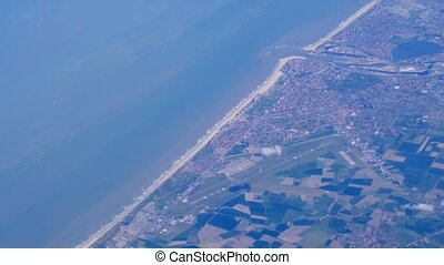 Aerial view of farmland area, cities and sea water landscape from airplane