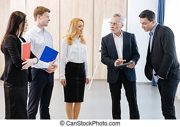 Serious confident man having a briefing with his colleagues...