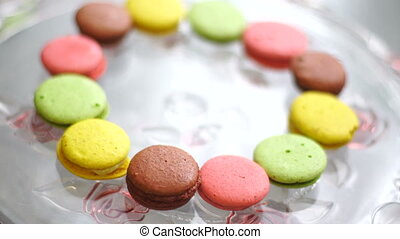 girl picks up macaroon cookies from a plate close up