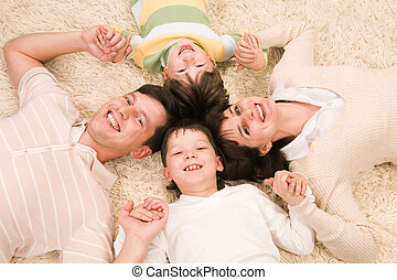 Family - Above view of cheerful parents with their two sons...