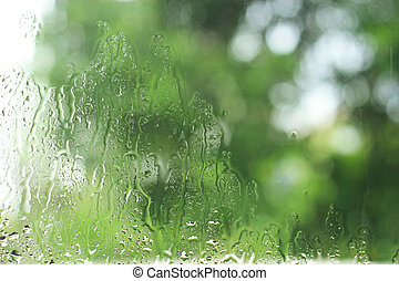 rain drops on window with green nature background in Blur