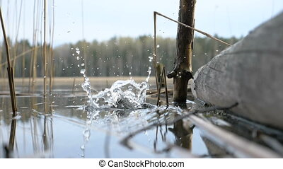 Water splash of cone drop from the hand to the river - slowmotion 180 fps