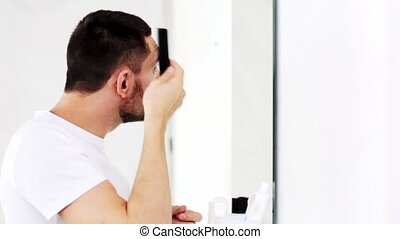 happy man brushing hair with comb at bathroom - beauty,...