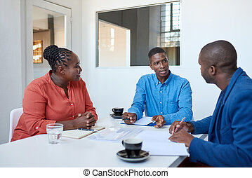 Three African coworkers discussing paperwork in an office