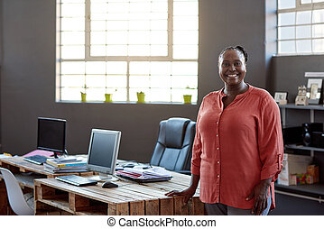 Smiling African businessman standing at her desk in an office