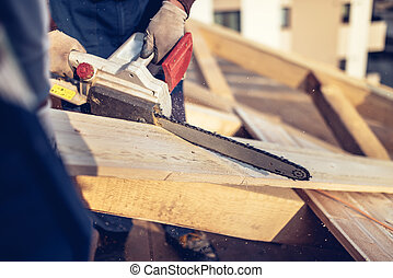 industrial construction workers cutting timber wood with chainsaw. Men sawing using electrical chainsaw at roof construction