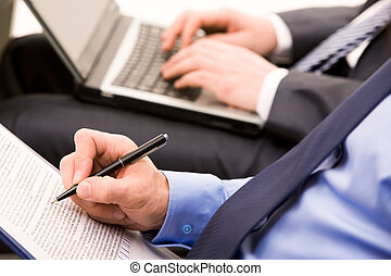Written work - Close-up of ceo hand with pen making notes at...