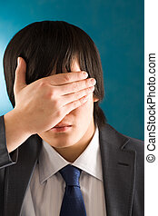 Hiding face - Portrait of young businessman hiding his face...