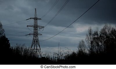 Time lapse of nightfall with clouds and transmission tower -...