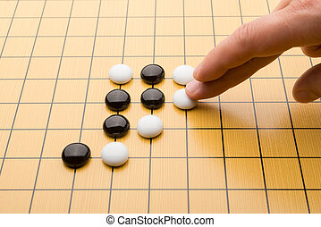 hand putting down piece of GO on board