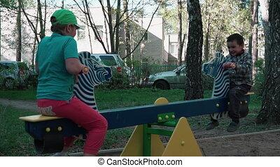Happy children ride on the swings (slow motion) - Happy boy...