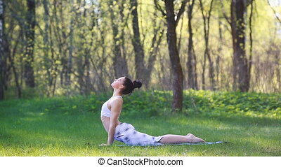 Young woman doing yoga exercises in the summer city park....