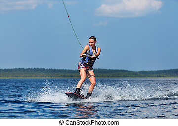 slim woman riding wakeboard on wave of boat - Young pretty...