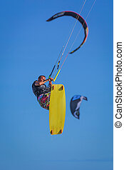 Young atletic man riding kite surf on a sea in Vietnam