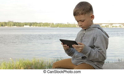 A boy is playing on a tablet near the sea - A boy with a...