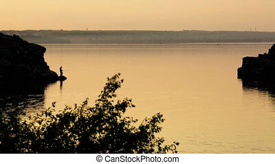 Silhouette of a fisherman fishing on bank of river at sunset