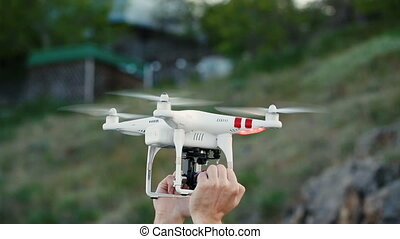 Men's hands hold drone and drone soars into the sky - Men's...