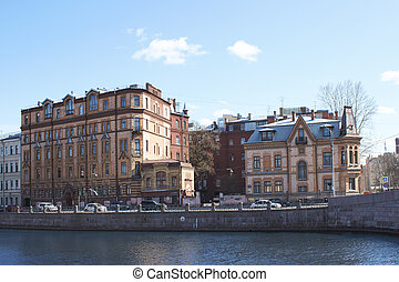 Several city houses on the river bank.