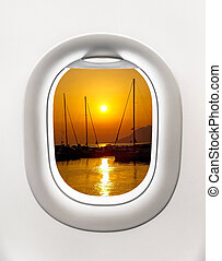 Looking out the window of a plane to the sunset in the...