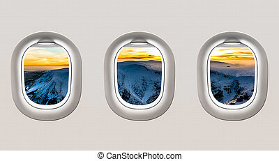 Looking out the windows of a plane to the winter mountains...