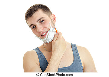 a cheerful young man with foam on his face worth bending head smiling and shaves his beard is isolated on a white background