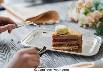Hands going to eat dessert, yellow mousse cake with almond...