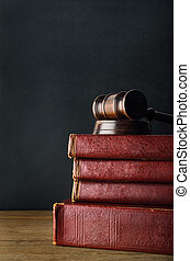 Wooden Gavel Topping Old Book Stack on Oak Desk with...