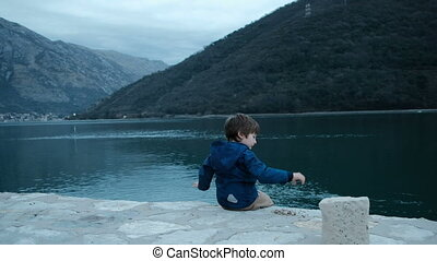 Little boy sits on shore and throws stones into water outdoors.