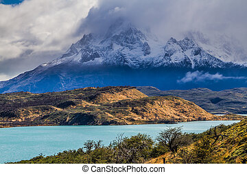 The magnificent cliffs of Los Cuernos in the clouds are...