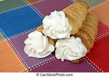 cream horns on place mat - cream horn pastry stacked on...