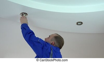 Young electrician man install or replace halogen spot light...