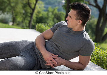 man doing morning yoga exercises - young handsome man doing...