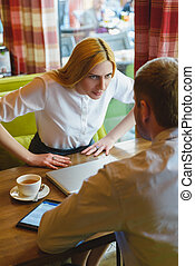 Business meeting in a cafe. Angry woman looks at man....
