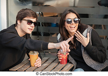 Happy young lady sitting outdoors with her brother drinking...