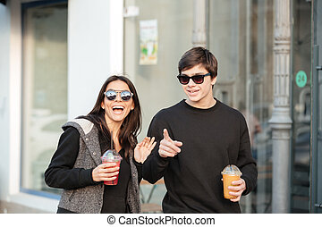 Happy young lady walking outdoors with her brother - Image...