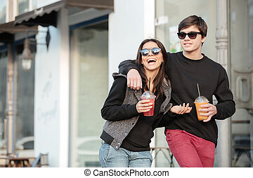 Smiling young lady walking outdoors with her brother
