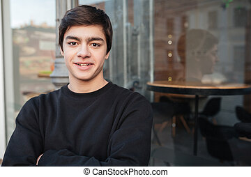 Young handsome man looking camera while standing near cafe