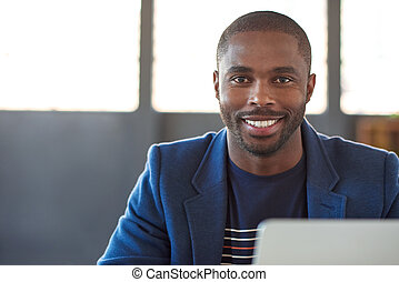 Smiling African businessman working on a laptop in an office