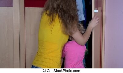 Pretty woman with her toddler child hiding in closet...