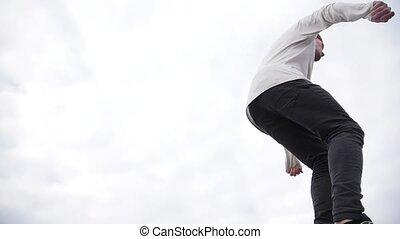 Urban teen acrobatics - teenager jumps a flip at park,...
