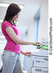 pretty young woman using a copy machine shallow DOF; color...