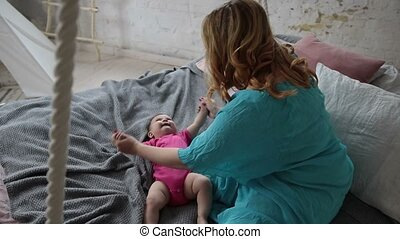 Mother massaging and exercising her little baby - Young...