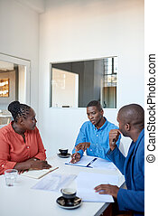 African business colleagues discussing paperwork in an office