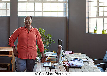 Smiling African businesswoman standing at her desk in an office